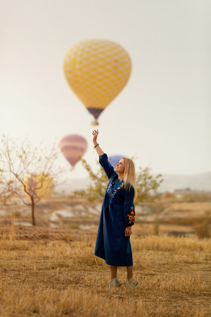 Photo for Beautiful Woman Trying To Reach Hot Air Balloon In Sky With Hand. High Resolution - Royalty Free Image