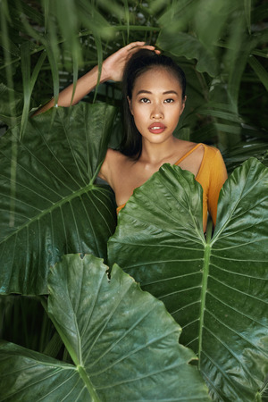 Photo for Natural beauty. Woman with beautiful face behind tropical leaves. Portrait of beautiful asian girl with and natural makeup behind jungle leaves in nature - Royalty Free Image