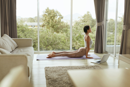 Foto de Girl doing yoga training, stretching body at home with computer. Beautiful asian woman practices cobra pose on yoga mat with laptop near window in living room in morning - Imagen libre de derechos