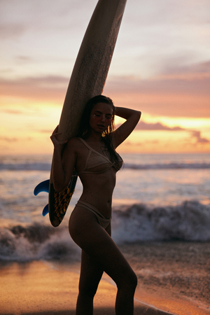 Photo pour Summer. Surfer girl silhouette with surf board on sunset beach. Shape of woman with surfboard on colorful sky and sea background - image libre de droit