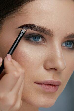 Foto de Eyebrow coloring. Woman applying brow tint with makeup brush closeup. Girl model using liquid peel-off brow gel, beauty product on eyebrows - Imagen libre de derechos
