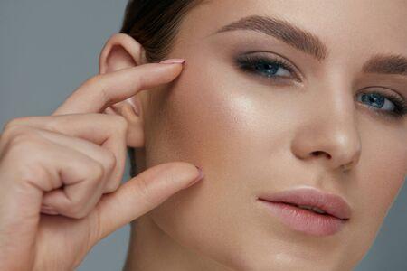 Foto de Beauty face makeup. Woman with beautiful eyes and eyebrows make-up closeup. Girl model with fingers near facial skin  - Imagen libre de derechos