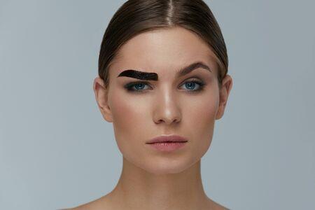 Foto de Beauty makeup. Woman coloring eyebrow with gel tint portrait. Girl model setting liquid peel-off brow gel on eyebrow - Imagen libre de derechos