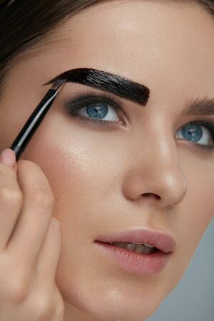 Photo pour Eyebrow coloring. Woman applying brow tint with makeup brush closeup. Girl model using liquid peel-off brow gel, beauty product on eyebrows - image libre de droit