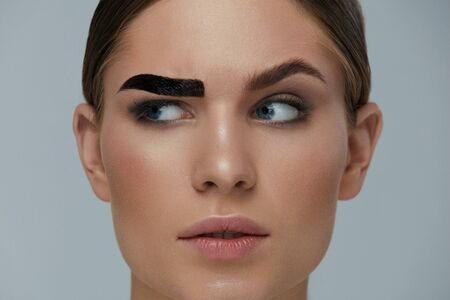 Photo pour Beauty makeup. Woman coloring eyebrow with gel tint closeup. Girl model setting liquid peel-off brow gel on eyebrow - image libre de droit