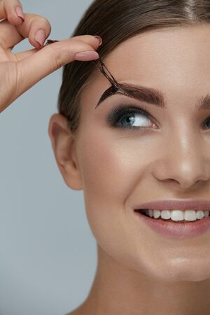 Foto de Eyebrow cosmetics. Woman taking off brow gel tint from eyebrow closeup. Girl model peeling off peel-off eyebrow beauty product - Imagen libre de derechos