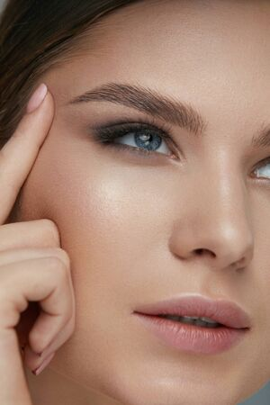 Photo pour Beauty face makeup. Woman with beautiful eyes and eyebrows make-up closeup. Girl model lifting eye skin with finger - image libre de droit
