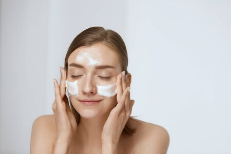 Foto de Face skin care. Woman applying facial cleanser on face closeup. Girl using cleansing cosmetic product on skin, washing face on light background - Imagen libre de derechos