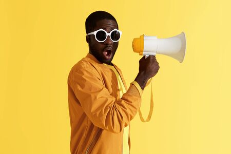 Photo for Surprised black man with megaphone on yellow background. Studio portrait of shocked african american male model in fashion sunglasses with loud speaker - Royalty Free Image