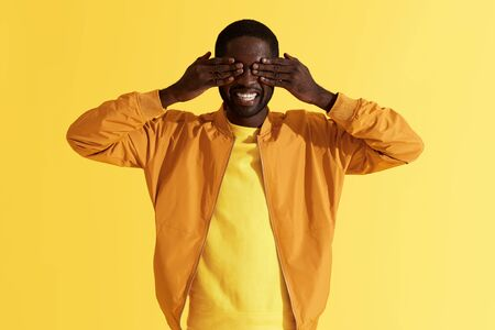 Photo for Surprise. Happy black man closing eyes with hands on yellow background. Portrait of smiling african american male model waiting for surprising gift, studio shot - Royalty Free Image