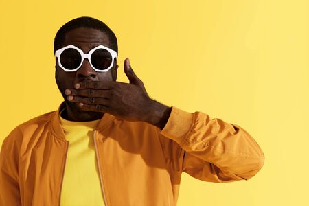 Photo for Surprise. Shocked man in fashion sunglasses on yellow background. Colorful portrait of amazed black male model with surprised face expression and hand closing mouth at studio - Royalty Free Image