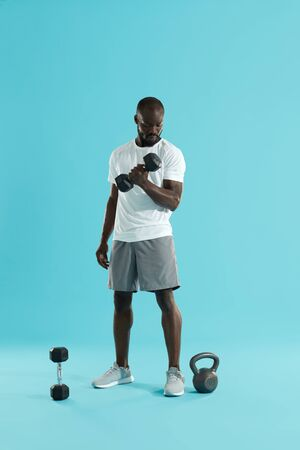 Foto de Exercise. Sports man doing dumbbell biceps workout on colorful background. Fitness male model in stylish active wear exercising, doing dumbbell curl - Imagen libre de derechos