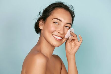 Foto de Face skin care. Smiling woman using oil blotting paper portrait - Imagen libre de derechos
