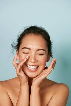 Foto de Beauty face. Smiling asian woman touching healthy skin portrait - Imagen libre de derechos