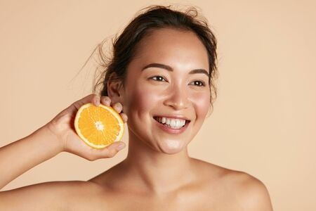 Photo pour Beauty. Smiling woman with radiant face skin and orange portrait - image libre de droit