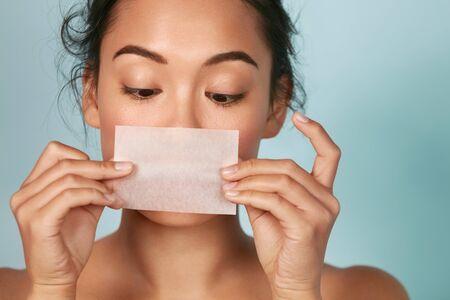 Photo pour Skin care. Woman holding facial oil blotting paper portrait - image libre de droit