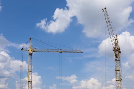 Photo pour Industrial construction building cranes against blue cloudy sky in background - image libre de droit