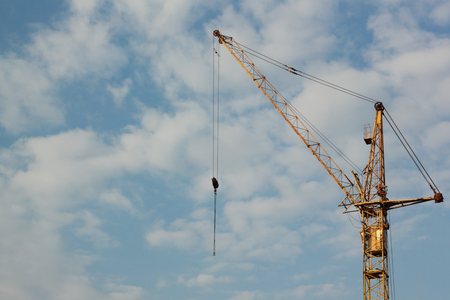Photo pour Industrial construction building crane against blue cloudy sky in background - image libre de droit