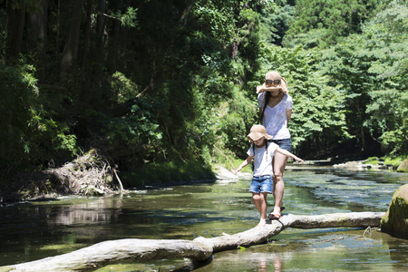 Photo for Mother and daughter playing in mountain stream - Royalty Free Image