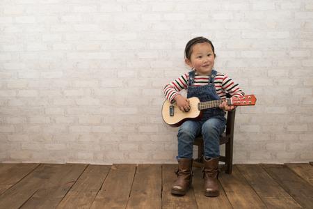 Photo pour Little girl plays guitar - image libre de droit