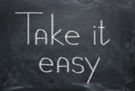 Photo pour Take it easy - inscription in chalk on a blackboard. Relax concept. - image libre de droit