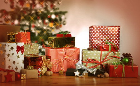 Photo for many Christmas presents on a table in the background a Christmas tree - Royalty Free Image