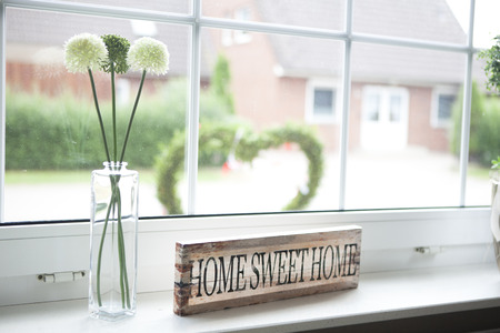 on a window sill in the house is a sign with the text home sweet home