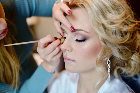 Foto de Wedding makeup artist making a make up for bride. - Imagen libre de derechos