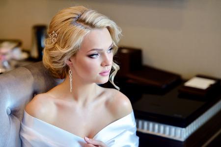 Foto de Beauty bride in dressing gown with bridal makeup indoors. - Imagen libre de derechos