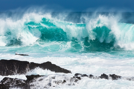 Turquoise rolling wave slaming on the rocks of the coastline
