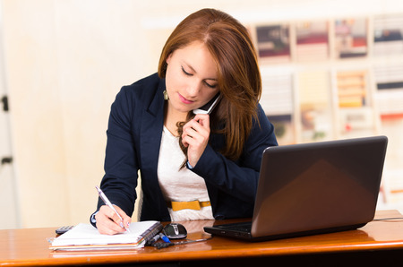 Photo for portrait of beautiful young secretary working from desk talking on cell phone - Royalty Free Image