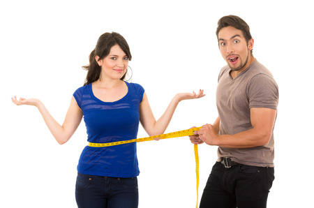 Foto de handsome open mouthed man holding measuring tape around thin fit young girl\'s stomach concept of dieting fitness weightloss  isolated on white - Imagen libre de derechos