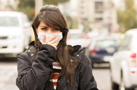 Foto de portrait of young girl walking wearing a mask in the city street concept of  pollution - Imagen libre de derechos
