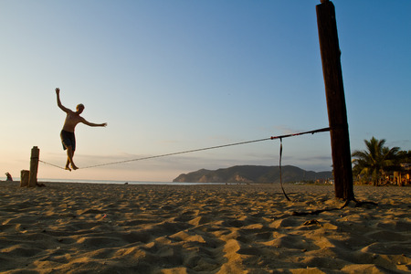 Foto de MANABI, ECUADOR - JUNE 5, 2012: Unidentified young man balancing on slackline at a beach in Manabi. - Imagen libre de derechos