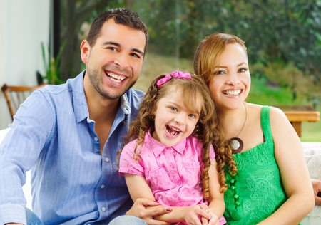 Proud happy hispanic parents posing with little cute girl wearing pink clothes in front of window garden background.