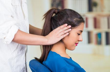 Foto de Attractive brunette office woman wearing blue sweater sitting by desk receiving head massage, stress relief concept. - Imagen libre de derechos