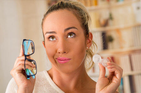 Foto de Young blonde woman holding contact lens case on hand and holding in her other hand a blue glasses on blurred background., eyesight and eyecare concept - Imagen libre de derechos