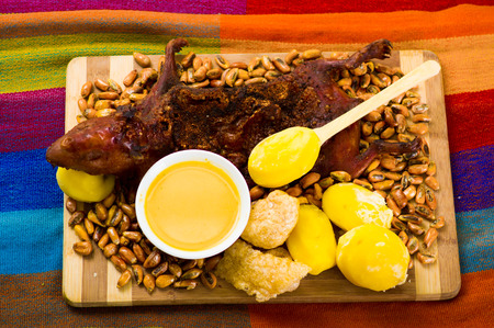 Traditional ecuadorian dish, grilled guinea pig spread out onto wooden board, tostados, bacon skin and lemons on the side, seen from above