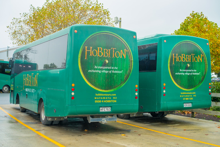 Photo for NORTH ISLAND, NEW ZEALAND- MAY 16, 2017: A full bus of tourists with a logo of famous movie, by the entrance to Hobbiton Village at Hobbiton Movie Set, back view - Royalty Free Image