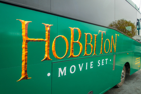 Photo for NORTH ISLAND, NEW ZEALAND- MAY 16, 2017: A full bus of tourists with a logo of famous movie, by the entrance to Hobbiton Village at Hobbiton Movie Set - Royalty Free Image