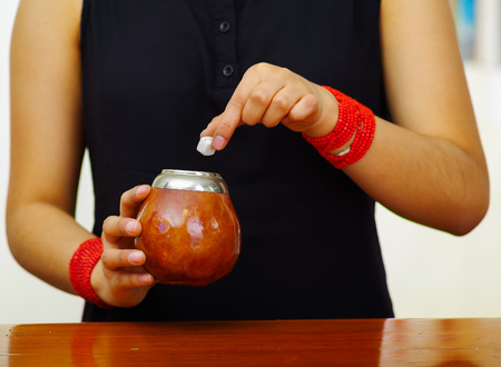 Photo for Woman holding traditional mate cup, addding sugar cube using other hand, south american herbal recreation drink - Royalty Free Image