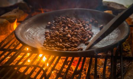 Foto de Close up of cacao bean inside of a metallic tray, over a wood stove, roasting cocoa beans - Imagen libre de derechos