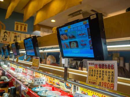 TOKYO, JAPAN -28 JUN 2017: Close up of assorted japanesse food over a table, with a screen with the menu, inside of a kaitenzushi conveyor belt sushi restaurant in Tokyo
