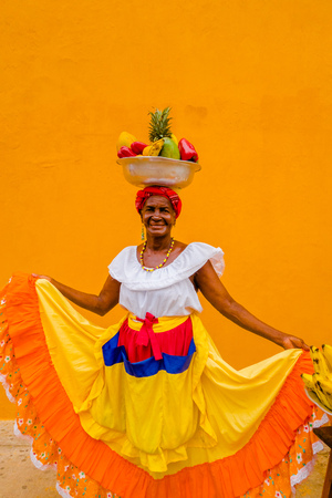 Photo pour Close up of woman in traditional costume with a basket of fruits in her head in a yellow background of Cartagena de Indias, Colombia - image libre de droit
