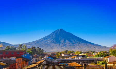 Photo pour Beautiful outdoor view of rooftops of the building in Antigua city with agua volcano mountain behind in a beautiful sunny day and blue sky - image libre de droit