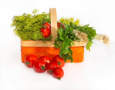 Composition with tomatoes and herbs in a basket for canning   parsley, onion, horseradish