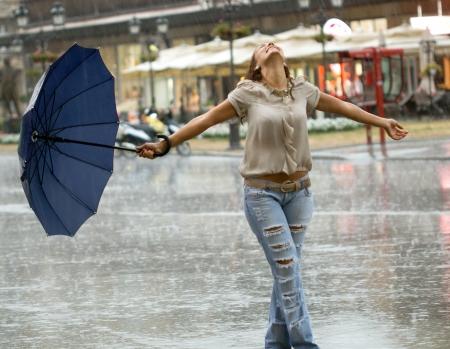 smiling woman with  umbrella enjoying in the rain