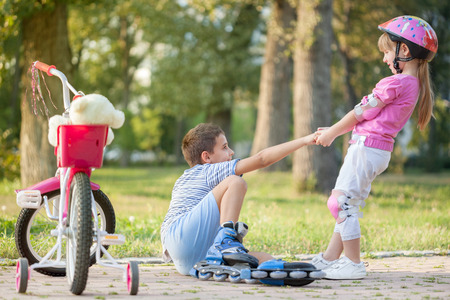 Photo pour girl in park, helps boy with roller skates to stand up  - image libre de droit