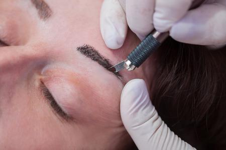 Foto de Cosmetologist applying permanent make up on eyebrows - Imagen libre de derechos
