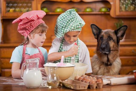 Foto de children preparing cookies in the kitchen, German Shepherd watching - Imagen libre de derechos